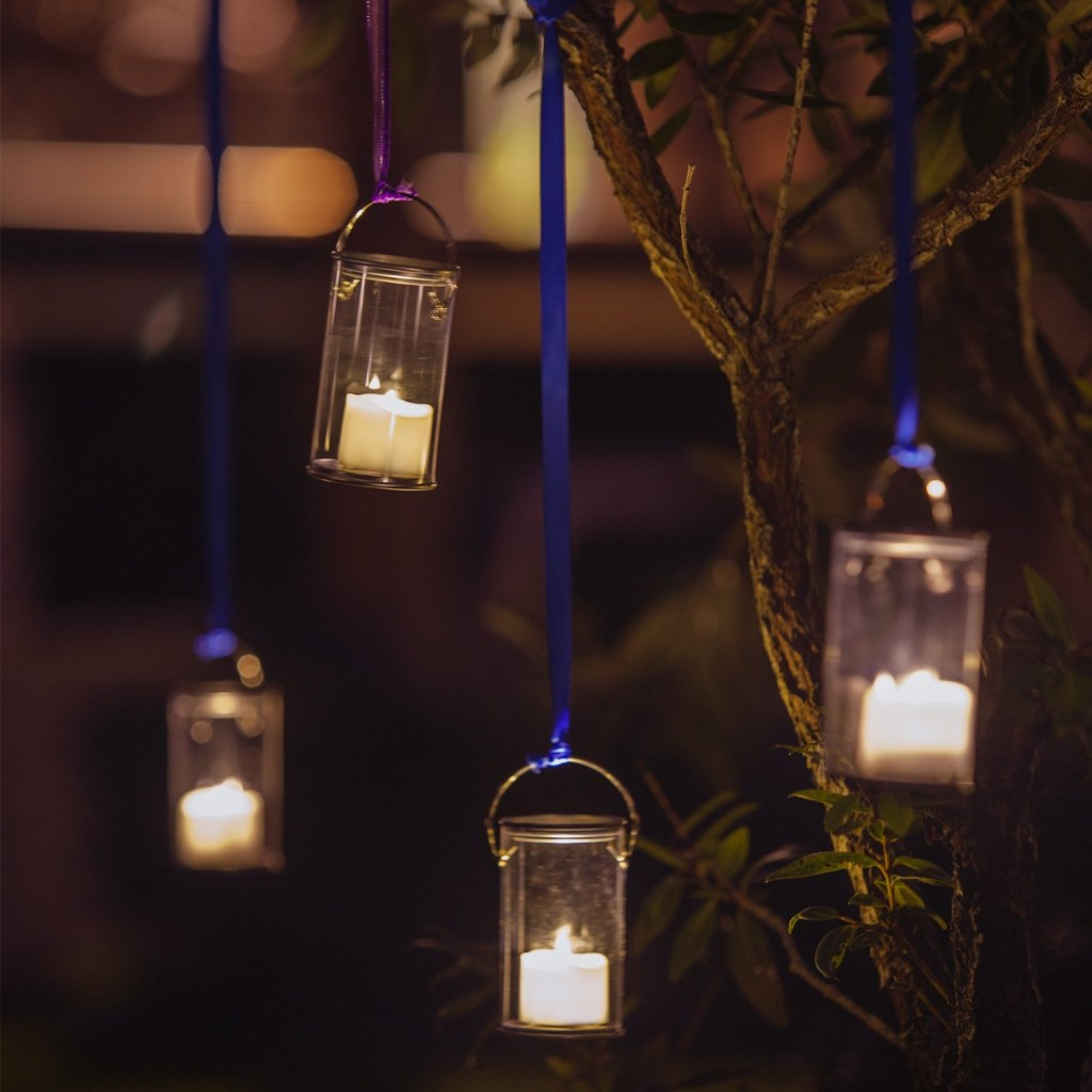 battery-operated candles hanging on trees